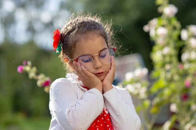 Retrato de uma menina linda e triste de óculos, com uma jaqueta branca, segurando seu rosto com as mãos