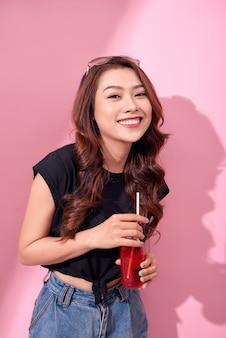 Retrato de uma menina linda feliz e fofa com roupas de verão casual beber refrigerante vermelho de uma garrafa com canudo sobre a parede rosa