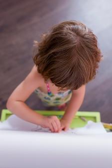 Retrato de uma menina linda jovem criança desenho na lousa em casa. felicidade e estilo de vida dentro de casa.