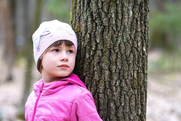 Retrato de uma menina linda jovem vestindo jaqueta rosa e boné, encostado em uma árvore na floresta, aproveitando o dia quente de sol