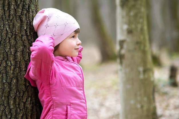 Retrato de uma menina linda jovem vestindo uma jaqueta rosa e boné encostado em uma árvore na floresta, aproveitando o dia quente de sol no início da primavera ao ar livre