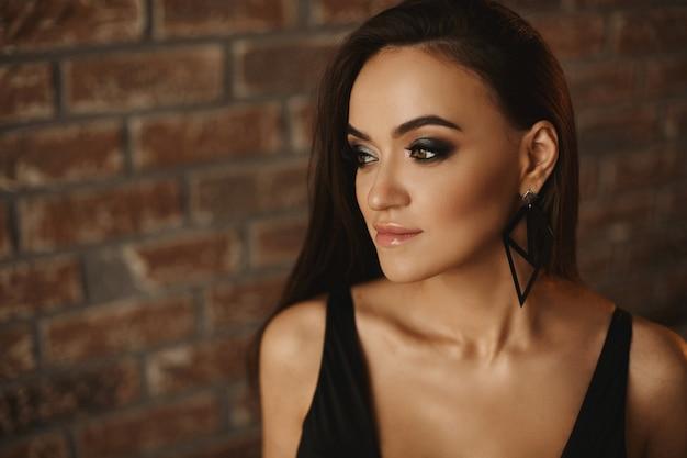 Retrato de uma menina linda modelo com incríveis olhos verdes, maquiagem perfeita e jovem de cabelos escuros ...