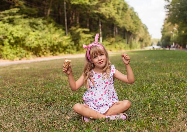 Retrato de uma menina loira bonita com sorvete em um passeio no parque.
