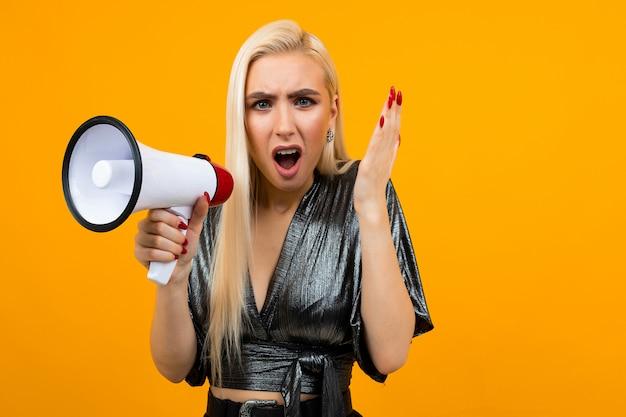 Retrato de uma menina loira caucasiana com raiva em uma blusa de grafite, contando a notícia com um megafone em uma parede amarela