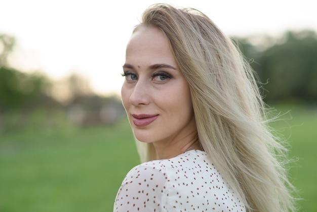 Retrato de uma menina loira caucasiana elegante e atraente, posando no verão na natureza. conceito de moda.