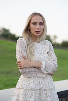 Retrato de uma menina loira caucasiana elegante e atraente, posando no verão na rua. conceito de moda.