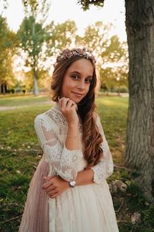 Retrato de uma menina loira com cabelo encaracolado com vestido de comunhão ao pôr do sol