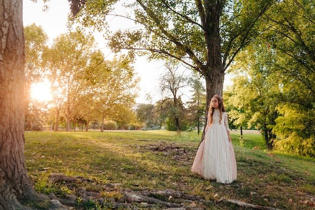 Retrato de uma menina loira com cabelo encaracolado com vestido de comunhão caminhando por entre algumas árvores