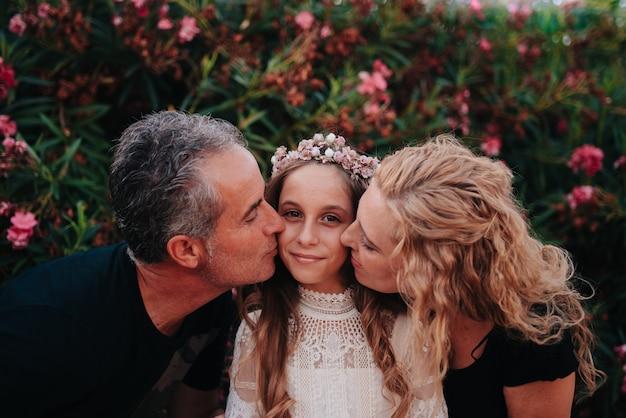 Retrato de uma menina loira com cabelo encaracolado vestida com um vestido de comunhão dando um beijo nos pais