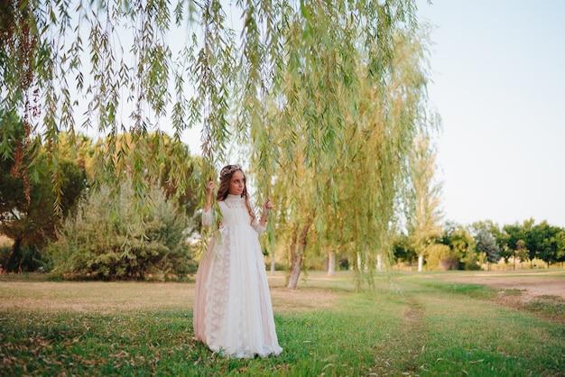 Retrato de uma menina loira com cabelo encaracolado vestida com vestido de comunhão