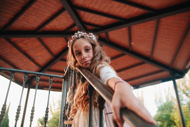 Retrato de uma menina loira com cabelos cacheados, vestida com um vestido de comunhão. copiar espaço