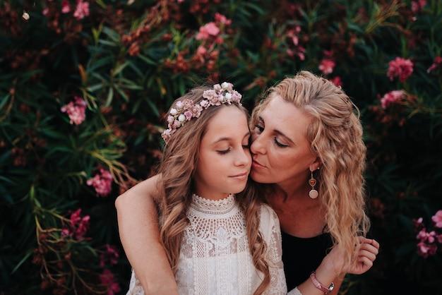 Retrato de uma menina loira com cabelos cacheados, vestida com um vestido de comunhão, dando um beijo em sua mãe
