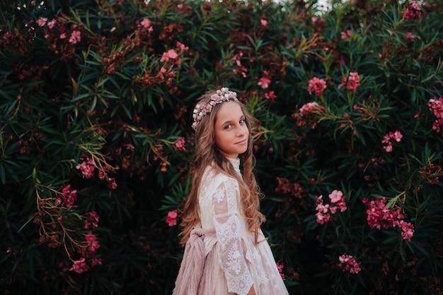 Retrato de uma menina loira com cabelos cacheados, vestida com um vestido de comunhão em um fundo de flores