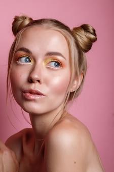 Retrato de uma menina loira com maquiagem de verão em uma parede rosa
