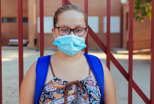 Retrato de uma menina loira com óculos, uma mochila azul e uma máscara facial. de volta à escola.