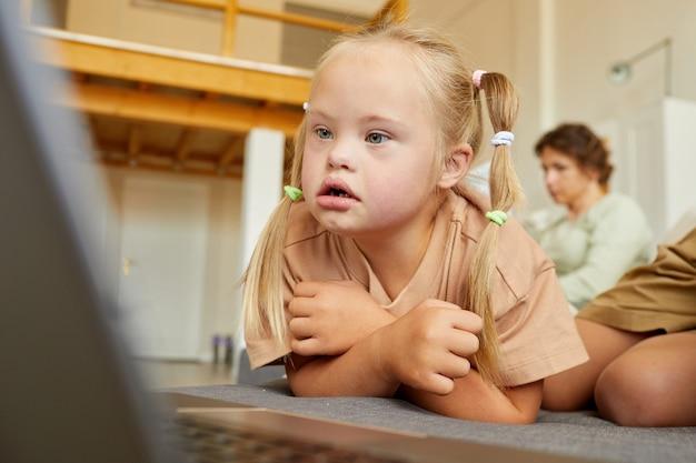 Retrato de uma menina loira com síndrome de down olhando para a tela do laptop enquanto assiste desenhos animados deitada no sofá em casa