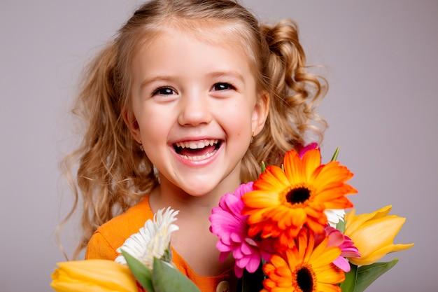 Retrato de uma menina loira com um buquê de flores da primavera em uma parede de luz