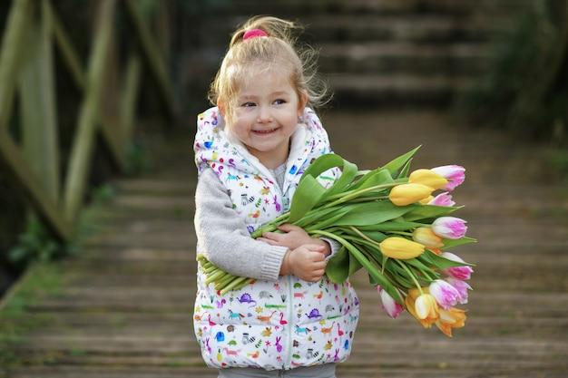 Retrato de uma menina loira com um buquê de tulipas nas mãos