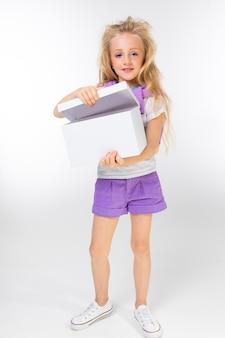 Retrato de uma menina loira com um suéter esportivo nos ombros abre uma caixa em branco