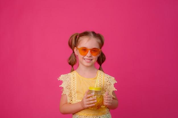 Retrato de uma menina loira em óculos de sol rosa com um frasco de vidro de coquetel de refrigeração.