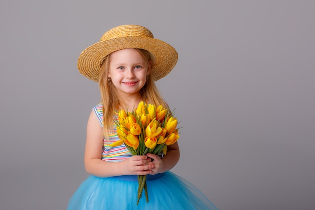 Retrato de uma menina loira em um chapéu de palha segurando um buquê de flores da primavera em um espaço em branco