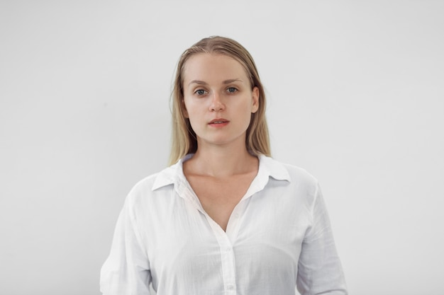 Retrato de uma menina loira em uma camisa branca na parede branca,