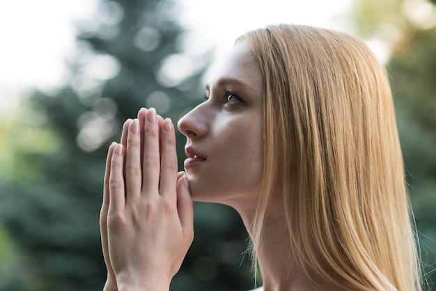 Retrato de uma menina loira espiritual, jovem e atraente. senhora ore a deus com esperança e fé