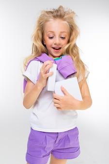 Retrato de uma menina loira feliz com moletom esportes lavanda nos ombros abre a caixa na parede branca