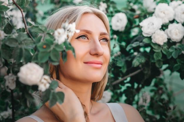 Retrato de uma menina loira linda com penteado no fundo de um arbusto de rosas brancas