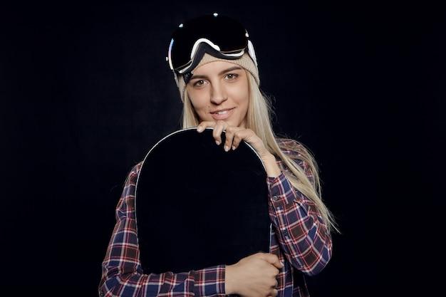 Retrato de uma menina loira na moda usando óculos de proteção e camisa xadrez segurando uma prancha de snowboard preta