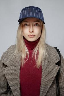 Retrato de uma menina loira no casaco de lã e chapéu de beisebol sem maquiagem.