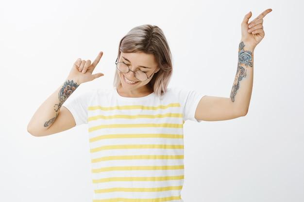 Retrato de uma menina loira positiva com óculos, posando no estúdio