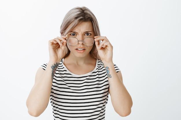 Retrato de uma menina loira preocupada com óculos, posando no estúdio
