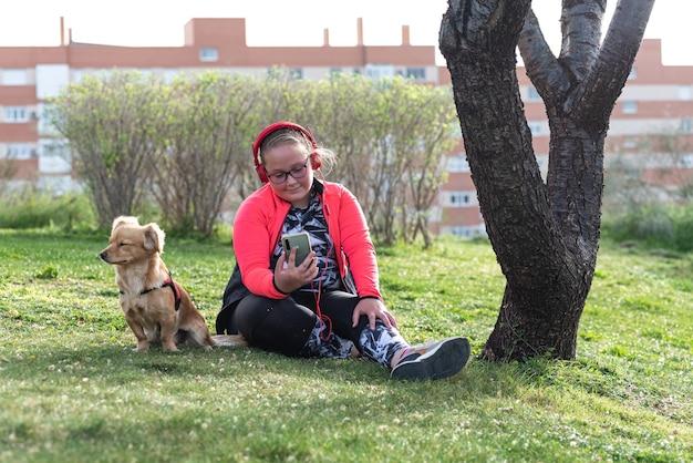 Retrato de uma menina loira rechonchuda com óculos, sentada no gramado com seu cachorro. ouvindo música em seu celular com fones de ouvido.