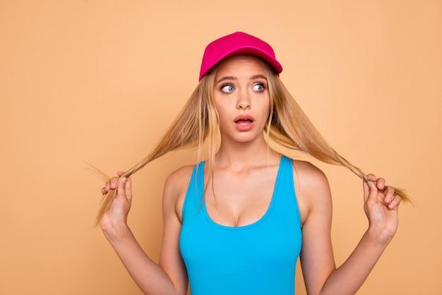 Retrato de uma menina loira segurando seus longos cabelos olhando para um espaço vazio