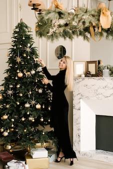 Retrato de uma menina loira sorridente com um vestido preto enfeita a árvore de natal