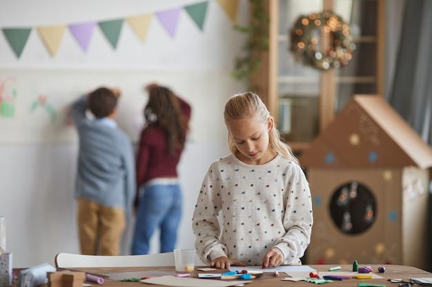 Retrato de uma menina loira sorridente em pé ao lado da mesa de trabalho e aproveitando a aula de arte na escola, copie o espaço