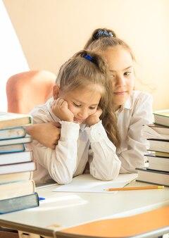 Retrato de uma menina mais velha abraçando um colega chateado na sala de aula