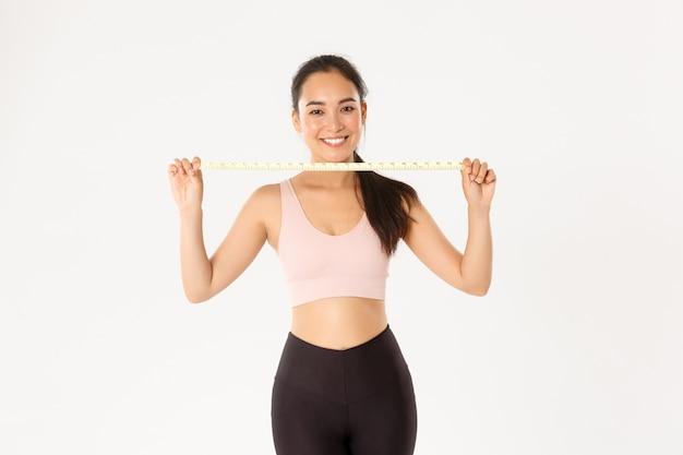 Retrato de uma menina morena asiática sorridente de esportes, atleta feminina em activewear mostrando a fita métrica, perdendo peso com exercícios, fundo branco.