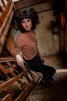 Retrato de uma menina morena na escadaria de uma casa abandonada, imagem com pouca luz