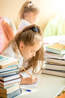 Retrato de uma menina morena sentada na sala de aula e escrevendo no livro de exercícios
