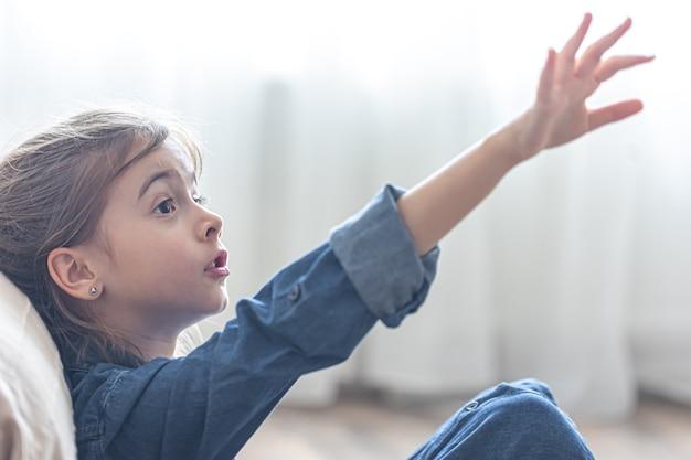 Retrato de uma menina, mostrando com entusiasmo algo com a mão à distância.