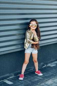 Retrato de uma menina na moda contra a parede cinza