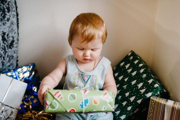 Retrato de uma menina na sala senta-se e desempacota presentes. conceito de aniversário festivo.