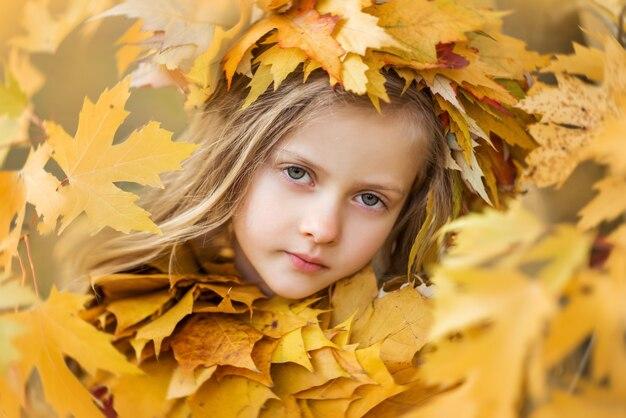Retrato de uma menina nas folhas de outono