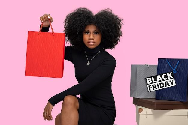 Retrato de uma menina negra sentada segurando uma sacola de compras isolada em um fundo azul