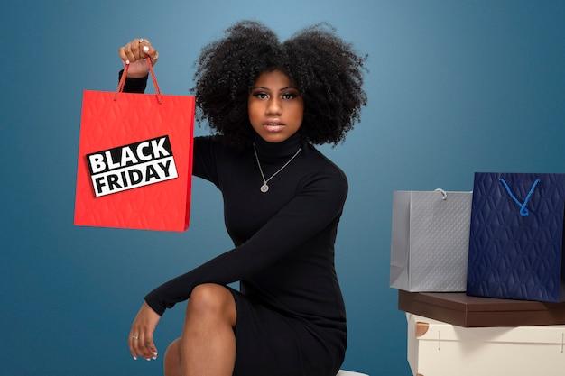 Retrato de uma menina negra sorridente segurando sacolas de compras isoladas sobre fundo azul