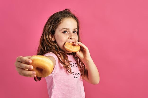 Retrato de uma menina oferecendo um donut em uma parede rosa