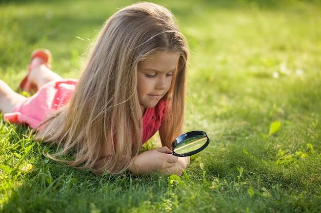 Retrato de uma menina olhando para a grama com uma lupa