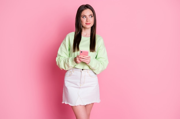 Retrato de uma menina pensativa blogando usar celular pensar pensamentos decidir que tipo de texto olhar copyspace usar roupas jeans branco verde isolado fundo de cor pastel